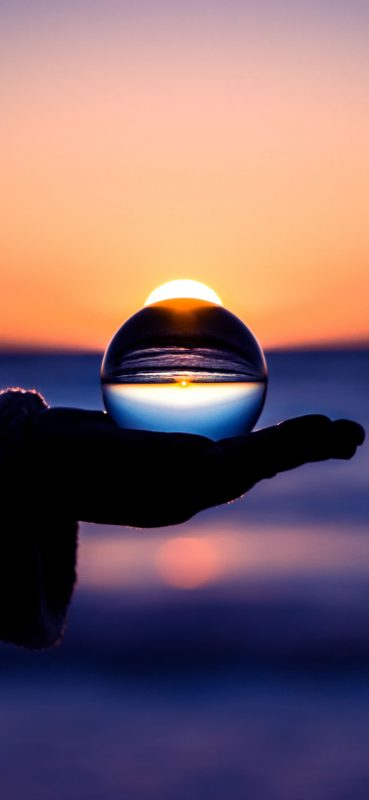 sunset-through-glass-ball-wallpaper-1080x2340